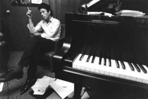 tom waits sitting by a piano and smoking a cigarette